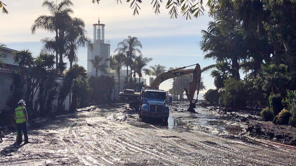 This photo provided by the Santa Barbara County Fire Department shows the cleanup of mud and debris in front of the Coral Casino and Biltmore Hotel along Channel Drive in Montecito, Calif., Wednesday, Jan. 10, 2018. (Mike Eliason / Santa Barbara County Fire Department via AP)