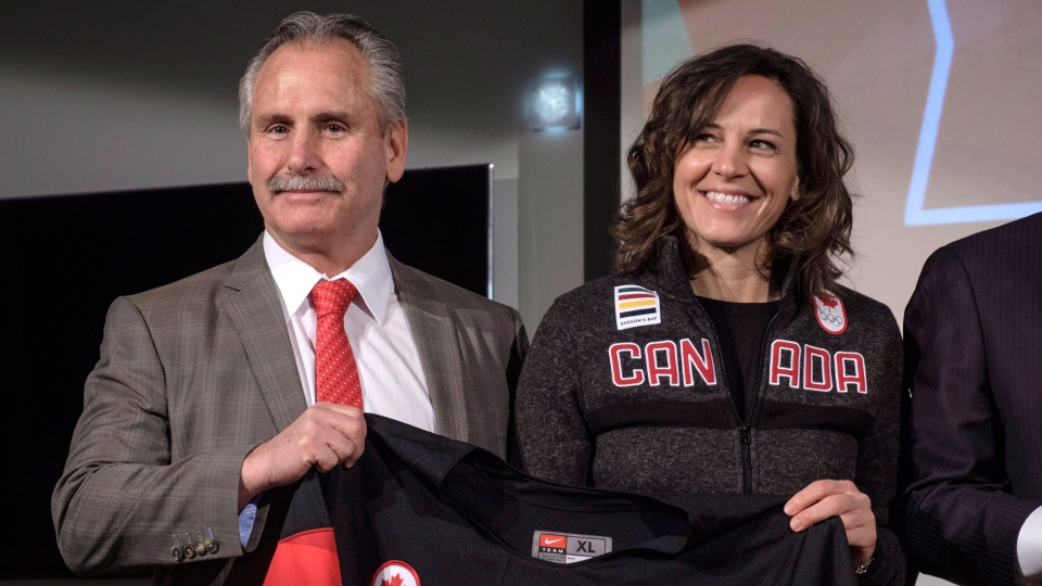 Head coach Hockey Canada Willie Desjardins and Team Canada chef de mission Isabelle Charest hold a jersey after announcing Canada's National Men's Team roster in Calgary, Thursday, Jan. 11, 2018. (THE CANADIAN PRESS/Jeff McIntosh)