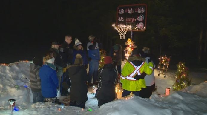 People gather at a roadside memorial erected shortly after a crash that killed eight people in Bathurst, N.B. just after midnight on Jan. 12, 2008. A candlelight vigil was held at the memorial on Jan. 12, 2018, to mark the 10th anniversary of the incident.