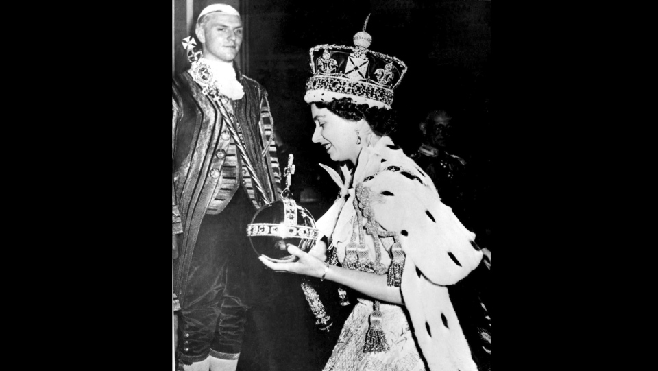 In this June 2, 1953 file photo, Queen Elizabeth II wearing the bejeweled Imperial Crown and carrying the Orb and Scepter with Cross, leaves Westminster Abbey, London, at the end of her coronation ceremony. (AP Photo)