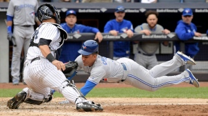 Toronto Blue Jays' Ezequiel Carrera scores on a sacrifice fly by Josh Donaldson as New York Yankees catcher Gary Sanchez (24) applies the late tag during the eighth inning of a baseball game Saturday, Sept.30, 2017, at Yankee Stadium in New York. (AP Photo/Bill Kostroun)