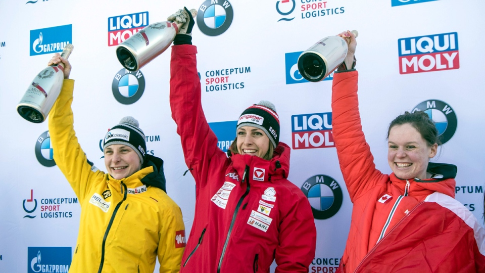 Second placed Tina Hermann of Germany, winner Janine Flock of Austria and third placed Elisabeth Vathje of Canada, from left, celebrate on the podium after the women's skeleton World Cup in St. Moritz, Switzerland, Friday, Jan. 12, 2018. (Urs Flueeler/Keystone via AP)