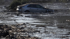 A car sits in flooded water in Montecito, Calif.