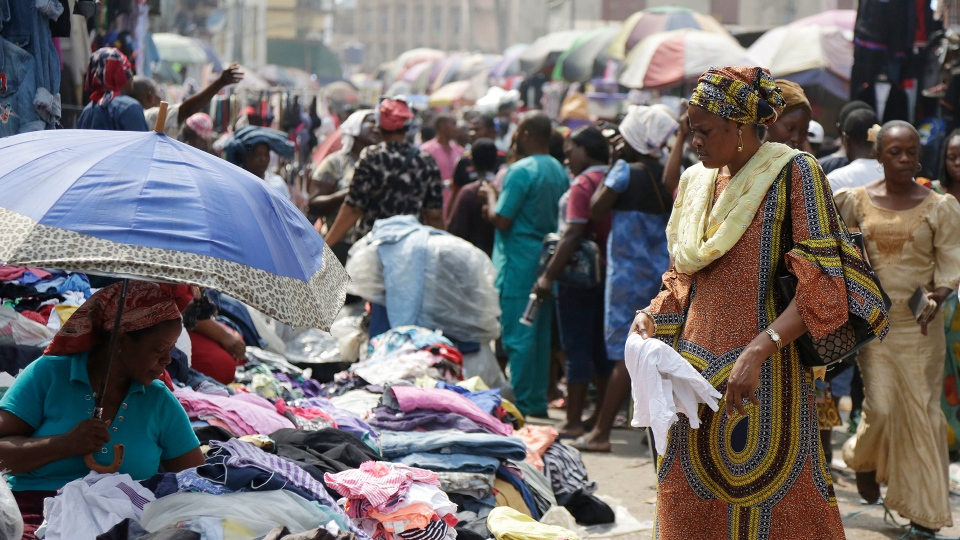 Pedestrians shop in a roadside market in Lagos, Nigeria, Friday, Jan. 12, 2018. (AP / Sunday Alamba)