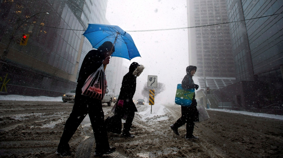 A man uses an umbrella to take cover from the blizzard like conditions in Toronto on Wednesday, March 12, 2014. (Nathan Denette / THE CANADIAN PRESS)