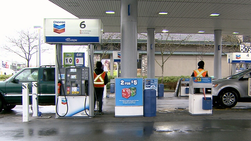 Attendants in bright vests are seen at gas pumps at a station in Richmond, B.C. on Thursday, Jan. 11, 2018.