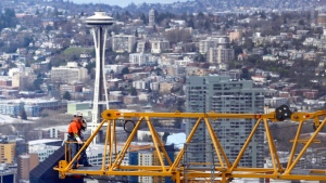 A worker talks on a radio as he stands at the end of a high-rise construction crane with the iconic Seattle Space Needle in the background, Thursday, Feb. 16, 2017. (THE CANADIAN PRESS/AP/Ted S. Warren)