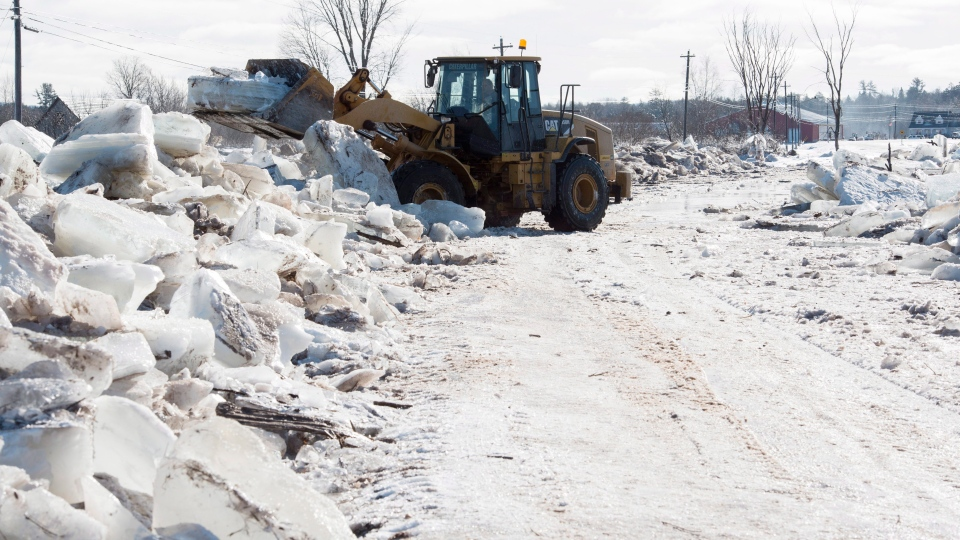 Tim McCann uses a front end loader to remove ice off of Route 101 in Hoyt, N.B., on Sunday, January 14, 2018. Heavy rain flooded the road on Saturday floating large ice onto the road and dropping temperatures then froze the water overnight into Sunday morning. THE CANADIAN PRESS/Stephen MacGillivray