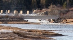Water from the East Branch dam rushes past an old generating station near an evacuated community in Musquash, N.B., on Sunday, January 14, 2018. THE CANADIAN PRESS/Stephen MacGillivray