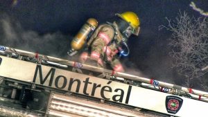 A firefighter climbs down a ladder while battling a house fire on Armand Bombardier Blvd. on Jan. 15, 2018 (CTV Montreal/Cosmo Santamaria)