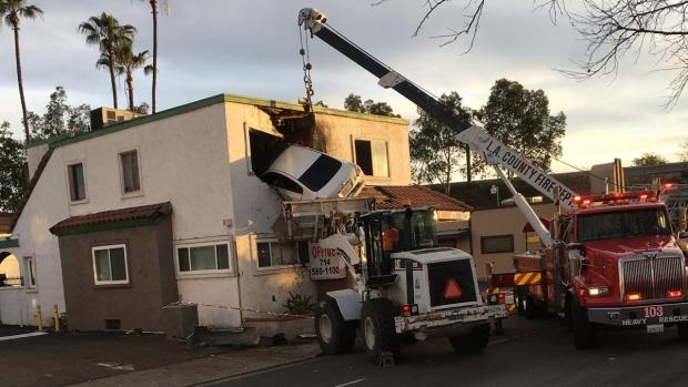 A vehicle that crashed into a building hangs from a second storey window in Santa Ana, Calif., on Jan. 14, 2018.  (Capt. Stephen Horner / Orange County Fire Authority via AP)