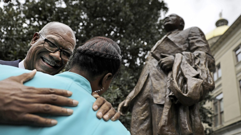 State Rep. Calvin Smyre, D - Columbus, left, embraces the Rev. Bernice King, daughter of the Rev. Martin Luther King Jr., at a statue paying tribute to Martin Luther King Jr. in Atlanta, on Aug. 28, 2017. (David Goldman / AP)
