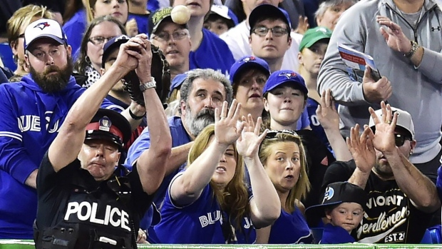 A police officer tries to catch a foul ball at Rogers Centre in Toronto, on May 14, 2017. (Frank Gunn/The Canadian Press via AP, File)