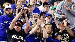 In this May 14, 2017, file photo, a police officer tries to catch a foul ball during seventh inning of a baseball game between the Toronto Blue Jays and Seattle Mariners in Toronto. The Blue Jays announced Monday, Jan. 15, 2017, they will extend the protective netting at Rogers Centre to the outfield end of each dugout this season and increase the height of netting behind home plate by approximately 10 feet to 28 feet. (Frank Gunn/The Canadian Press via AP, File)