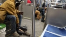 A homeless man removes his tattered shoes to put on a pair of winter boots given to him by another passenger on Chicago's subway system Friday, Jan. 12, 2018. (Jessica Bell / Facebook)