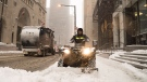 A worker clears sidewalks on a four-wheeler in Toronto's financial district on Thursday, Dec. 11, 2014. (The Canadian Press/Graeme Roy)