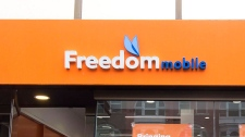 A man enters the store at the new rebranding sign of Freedom Mobile in Toronto on Thursday, November 24, 2016. Wind Mobile, Canada's fourth-largest mobile phone company, is changing its name to Freedom Mobile and moving to upgrade its network. THE CANADIAN PRESS/Nathan Denette