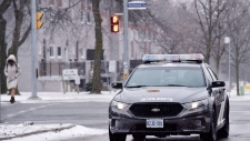 A police car passes through an intersection near P