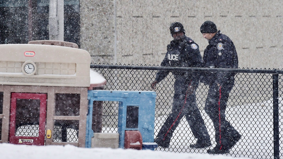 Two police officers walk around Pauline Johnson Junior Public School in Toronto on Monday, January 15, 2018. A Toronto police investigation has concluded that an incident reported by an 11-year-old girl who claimed her hijab was cut by a scissors-wielding man as she walked to school did not happen. THE CANADIAN PRESS/Frank Gunn