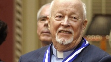 Father Emmett Johns, known as Pops in Montreal, smiles at the end of a ceremony where he was decorated with the Ordre National du Quebec as a Grand Officer, Tuesday, Oct. 28, 2003. at the Quebec Legislature. THE CANADIAN PRESS/ Jacques Boissinot