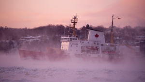 The Canadian Coast Guard ice breaker Pierre Radisson plows through the ice on the Saint Lawrence River at sunrise as extreme cold hits the region Friday, February 6, 2015 in Quebec City. (Jacques Boissinot/THE CANADIAN PRESS)
