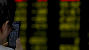 A man checks the stock index on his smartphone at a brokerage house in Beijing, Tuesday, Jan. 16, 2018. (AP Photo/Andy Wong)