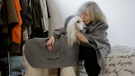 In this image taken on Thursday, Jan. 11, 2018, designer Giovanna Temellini kisses her dog Ulisse, an Afghan greyhound, wearing a winter coat created by Ms. Temellini, at the Temellini manufacture headquarters, in Milan, Italy. (AP Photo/Luca Bruno)