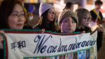 Women hold a quilt with messages written on it during a protest outside the site of a summit on North Korea being hosted by Canada and the U.S., in Vancouver, B.C. on Jan. 15, 2018. (THE CANADIAN PRESS/Darryl Dyck)