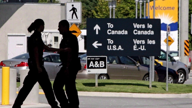 Canadian border guards are silhouetted at an inspection booth at the Douglas border crossing on the Canada-USA border in Surrey, B.C., on August 20, 2009. (THE CANADIAN PRESS/Darryl Dyck)