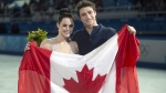 Tessa Virtue and Scott Moir pose with the Canadian flag in Sochi, on Feb. 17, 2014. (Paul Chiasson / THE CANADIAN PRESS)