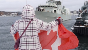 A family member holds a flag as HMCS St. John's heads to the Mediterranean Sea from Halifax on Jan.16, 2018. (THE CANADIAN PRESS / Andrew Vaughan)