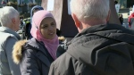 Fauzia Baig speaks with a man at an event in Waterloo where free cookies were handed out to spark discussion about Muslim beliefs and culture.