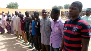 In this Monday, Jan.15, 2018, photo, people freed by Nigeria Army line up in Maiduguri Nigeria. Nigeria's army released 244 Boko Haram suspects who have denounced their membership of the deadly extremist group, Nigerian army officials said Tuesday. (AP Photo/Jossy Ola)