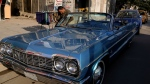 A man cleans a blue 1964 Chevrolet parked in front of the owner Saad al-Nuaimi's coffee shop in the northern Azamiyah neighborhood of Baghdad, Iraq on Wednesday, Jan. 10, 2018. (AP Photo/Khalid Mohammed)