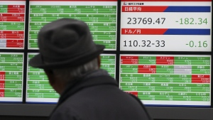 A man looks at an electronic stock board showing Japan's Nikkei 225 index at a securities firm in Tokyo Wednesday, Jan. 17, 2018. (AP Photo/Eugene Hoshiko)