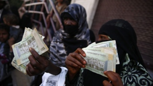 Women display paper currency after receiving cash support from UNICEF, in Sanaa, Yemen, on Nov. 14, 2015. (Hani Mohammed / AP)
