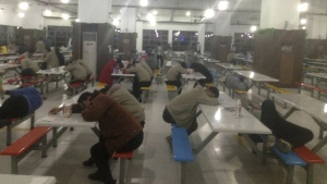 Workers rest at night in a cafeteria at a Catcher Technologies factory in Suqian, China, in Oct. 2017. (China Labor Watch via AP)
