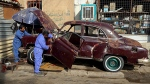 Mechanics work on Saad al-Nuaimi's badly damaged 1952 Chevrolet in Baghdad, Iraq, on Jan. 11, 2018. (Karim Kadim / AP)