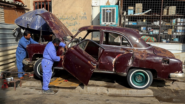 Mechanics work on Saad al-Nuaimi's badly damaged 1952 Chevrolet in Baghdad, Iraq, on Jan. 11, 2018. (Karim Kadim / AP)