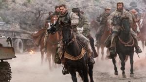 "This image released by Warner Bros. Entertainment shows Chris Hemsworth, center, in a scene from ""12 Strong."" (David James/Warner Bros. Entertainment via AP)"