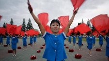 North Korean women wave flags cheering on their fellow countrymen as they start their day during morning rush hour on Wednesday, Sept. 28, 2016, in Pyongyang, North Korea. (AP Photo/Wong Maye-E)