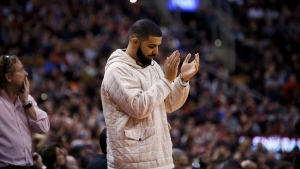 Toronto rapper Drake applauds during second half NBA basketball action between the Golden State Warriors and Toronto Raptors in Toronto on Saturday January 13, 2018. (THE CANADIAN PRESS / Cole Burston)