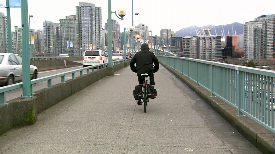 A cyclist is seen on the Cambie Street Bridge.