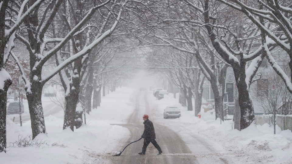 A woman uses a shovel to clear snow during a winter storm in Halifax on Wednesday, January 17, 2018. (THE CANADIAN PRESS/Darren Calabrese)