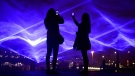 People take photos of the artwork light display entitled Waterlicht by Daan Roosegaarde at Granary Square in London, during the Lumiere London light festival, Wednesday Jan. 17, 2018.  (Kirsty O'Connor/PA via AP)