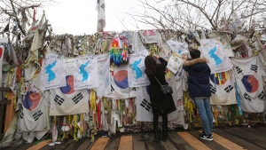 Visitors hang ribbons and unification flags wishing for reunification of the two Koreas on a border wire fence at the Imjingak Pavilion in Paju, near the border with North Korea, South Korea, Jan. 18, 2018. (AP Photo/Ahn Young-joon)