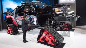 A worker cleans a GMC Sierra All Mountain truck in preparation for the Montreal Auto Show, Thursday, January 18, 2018 in Montreal. THE CANADIAN PRESS/Paul Chiasson