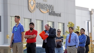 In this Wednesday, Aug. 2, 2017, file photo, applicants wait in line to enter a job fair at an Amazon fulfillment center, in Kent, Wash. (Elaine Thompson/AP Photo)