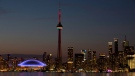In this July 26, 2015 file photo, the sun sets over the CN Tower and Rogers Centre during the closing ceremonies of the Pan Am Games in Toronto. Toronto's attractions are getting an extra dose of attention because the city is hosting the 2016 NBA All-Star game. (AP Photo/Rebecca Blackwell, File)