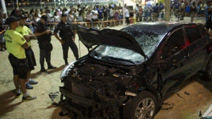 Police officers stand next to the a car that has driven into the crowded seaside boardwalk along Copacabana beach in Rio de Janeiro, Brazil, Thursday, Jan. 18, 2018. (AP Photo/Silvia Izquierdo)